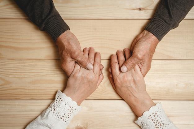 Старые руки пожилой пары вместе, взявшись за руки Premium Фотографии