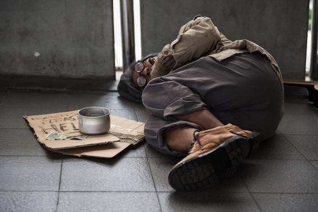 Old homeless man sleep on footpath Premium Photo