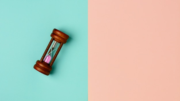 Old hourglass on blue and pink background Premium Photo