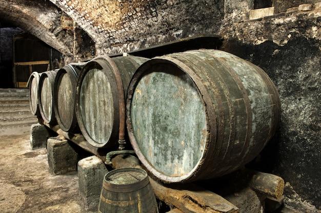 Old keg barrels in row in old wine cellar Premium Photo