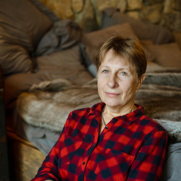 Old lady in sitting beside the bed in the chalet. portrait. Premium Photo