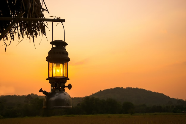 Old lantern hang a wood in sunset period Premium Photo