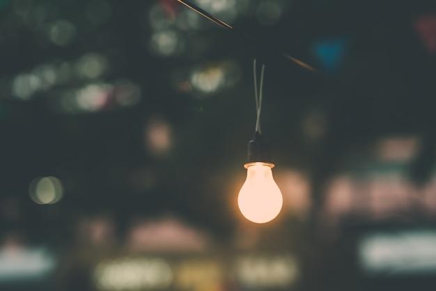 Old light bulb glowing in night. Premium Photo