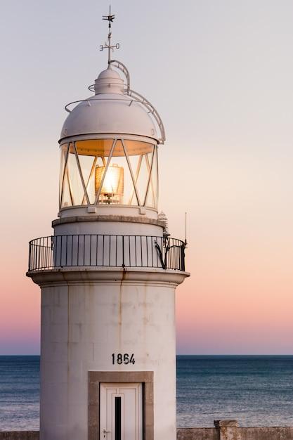 背景に美しい夕日と海岸の古い灯台 Premium写真