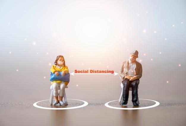 Миниатюрные старики и женщины, носящие маску и садящиеся на стул, держат дистанцию на публике, чтобы предотвратить вспышку коронирусного вируса covid-19, распространяющую пандемическую инфекцию. концепция социального дистанцирования. Premium Фотографии