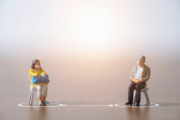 Миниатюрные старики и женщины, носящие маску и садящиеся на стул, держат дистанцию на публике, чтобы предотвратить вспышку коронирусного вируса covid-19, распространяющую пандемическую инфекцию. Premium Фотографии