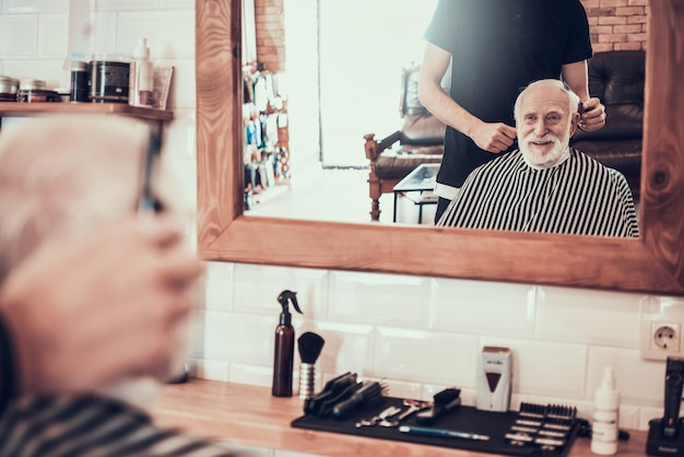 Old man came to young barber for style haircut Premium Photo