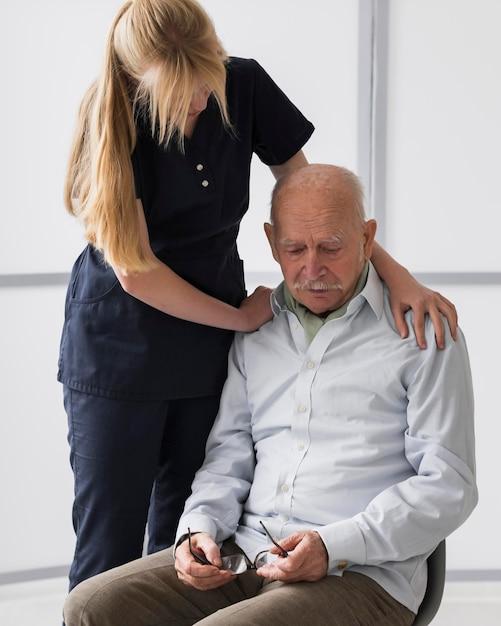 Uomo anziano che piange in una casa di cura con un'infermiera che lo consola Foto Gratuite
