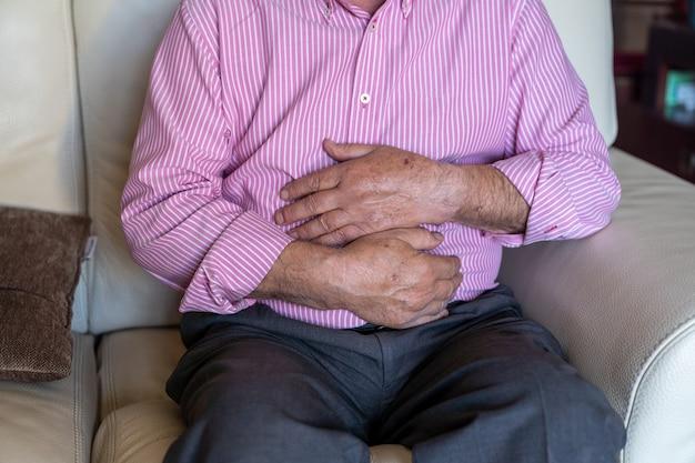 Old man feeling pain ache on his tummy Premium Photo