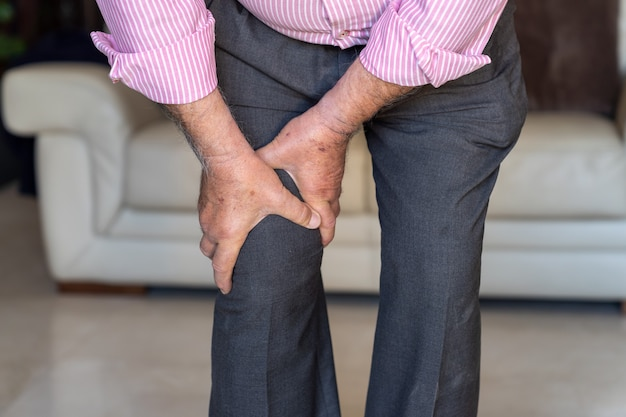 Old man feeling pain on his knee and touching it Premium Photo