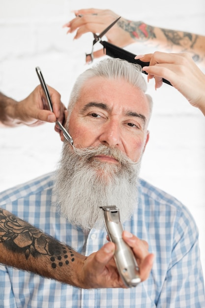 Old man getting hair and beard grooming Free Photo