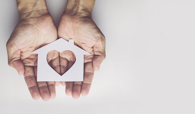 Old man hands holding small model family Premium Photo