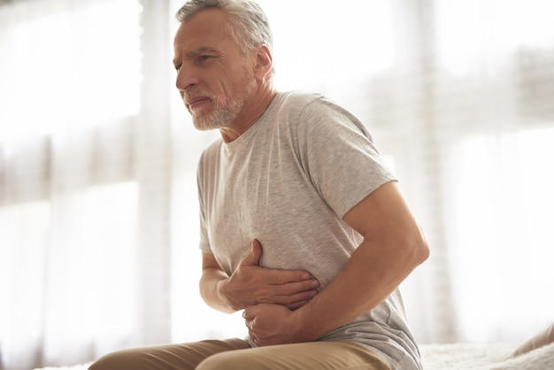 Old man holding belly stomach ache hurts patient. Premium Photo