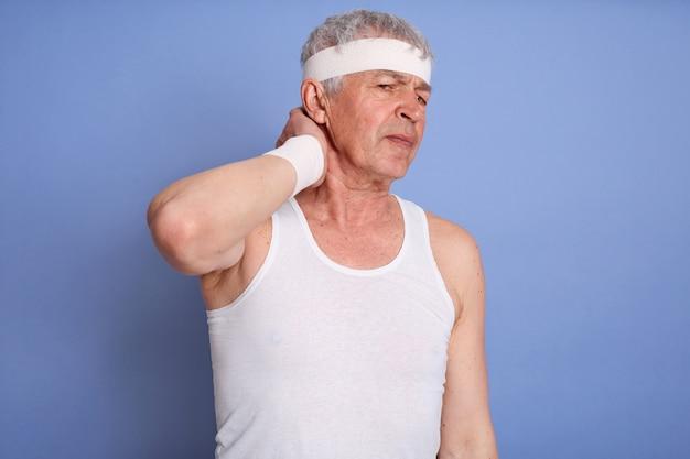 Старик в белой футболке держит шею от боли изолированной, касается ее шеи, травмирован во время спортивной тренировки, спортивный мужчина с повязкой для волос. Бесплатные Фотографии