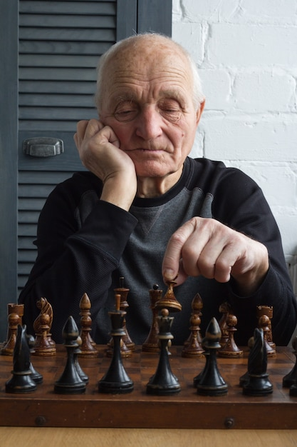 An old man is sitting in front of a chessboard Premium Photo