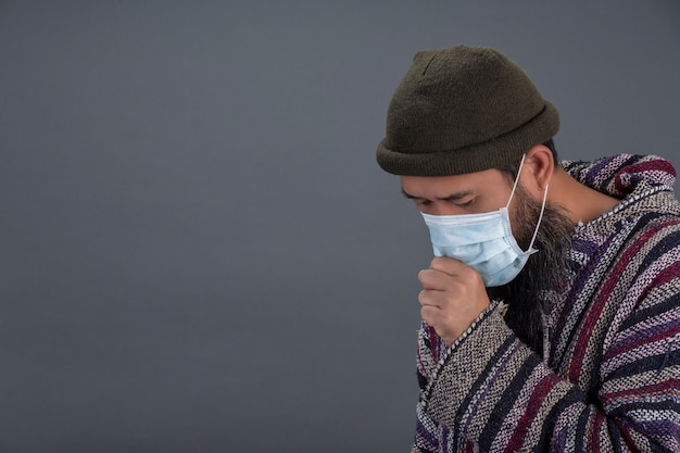 Old man is wearing mask while coughing on gray wall. Free Photo