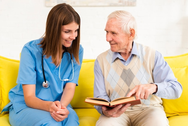 Old man looking on a book with a nurse Free Photo