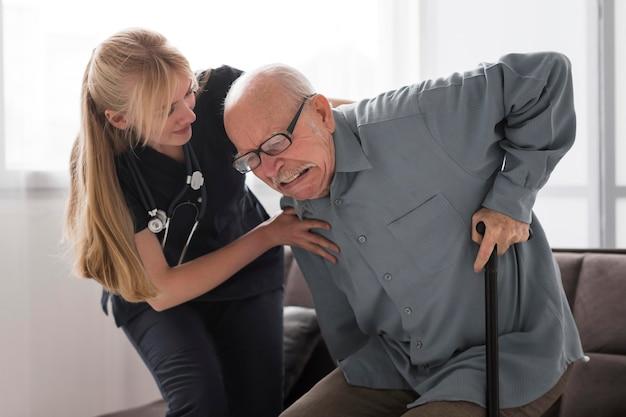 Uomo anziano che soffre aiutato dall'infermiera Foto Gratuite