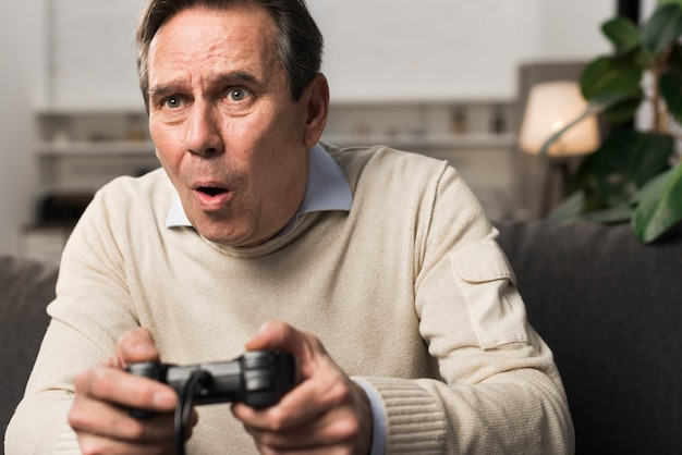 Old man playing videogame Free Photo