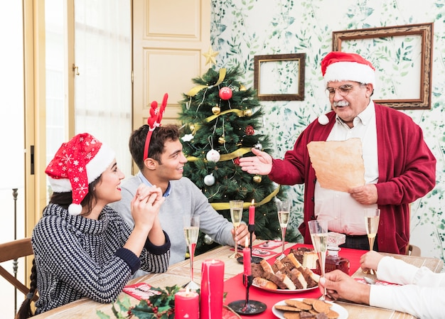 Old man reading from paper at christmas table Free Photo