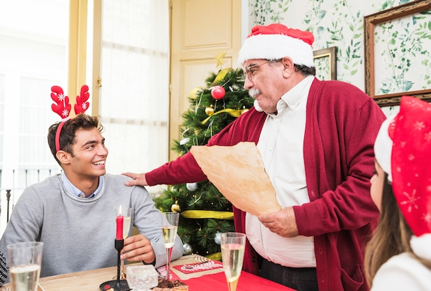 Old man in red reading from paper at festive table Free Photo