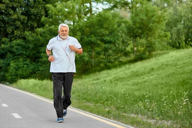Old man running on modern city park's racetrack. Premium Photo