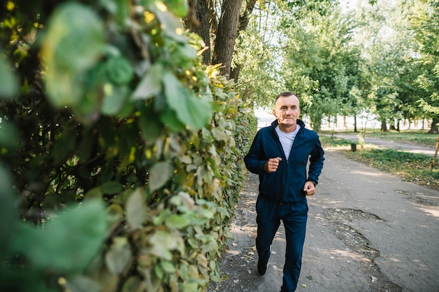 Old  man running outdoors in summertime Free Photo