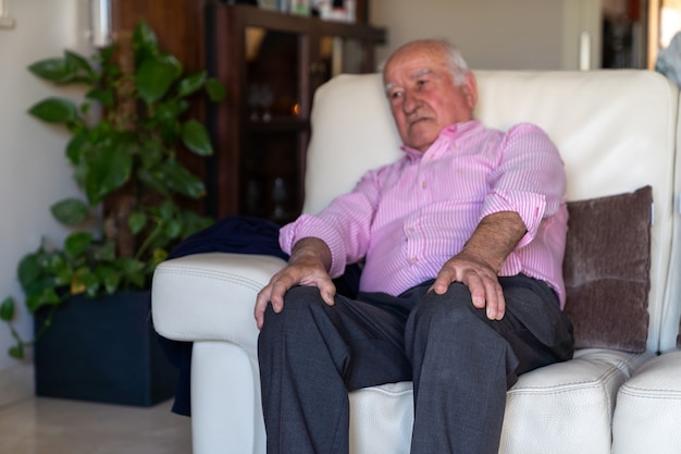 Old man sat on a sofa feeling pain and ache on knees Premium Photo