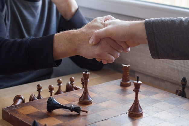 An old man shakes hands with an opponent in a game of chess Premium Photo