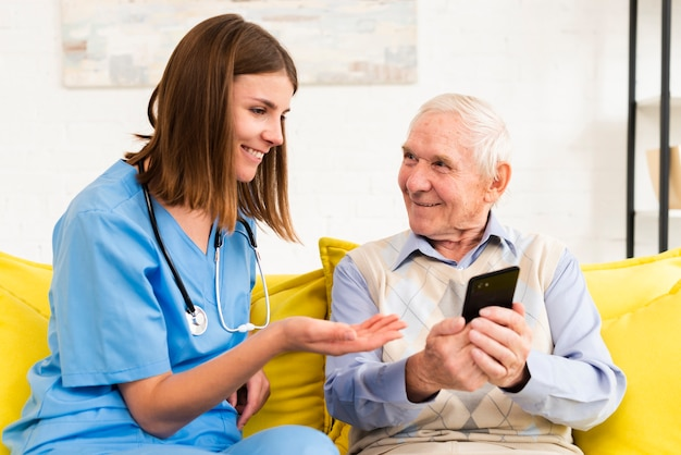Old man showing photos on phone to caregiver Free Photo