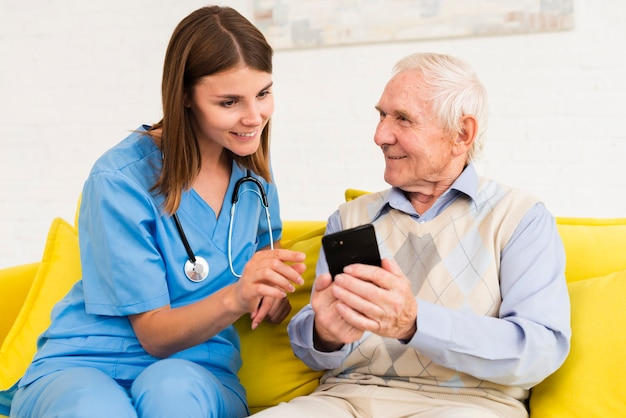 Old man showing photos on phone to nurse Free Photo