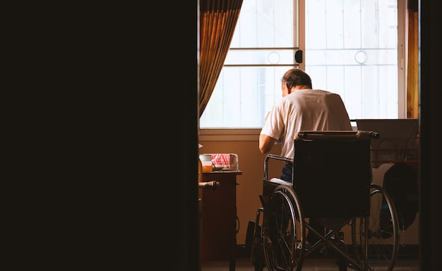 Old man sitting alone in a wheelchair at house Premium Photo
