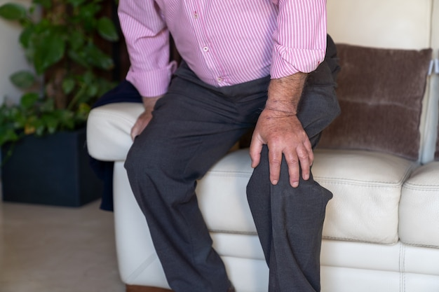 Old man sitting on sofa and feeling pain on his knee and s Premium Photo