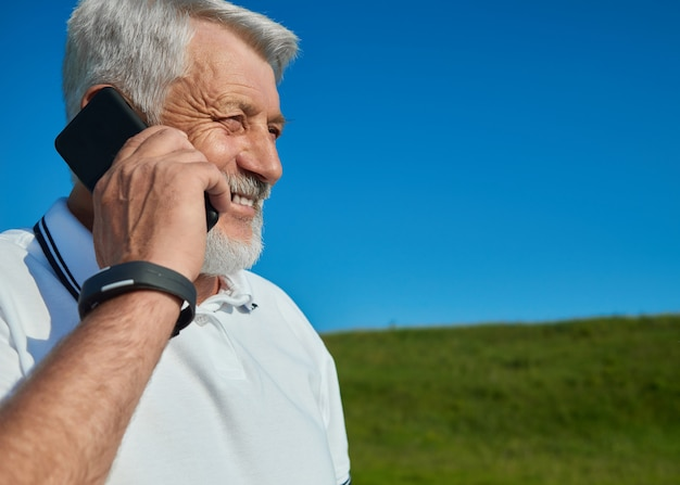 Old man talking on cell phone in the field. Premium Photo