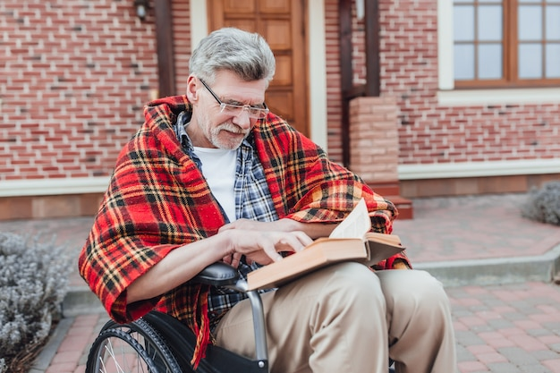 Old man on wheelchair reading interesting novel and posing to the camera near nursing home Premium Photo