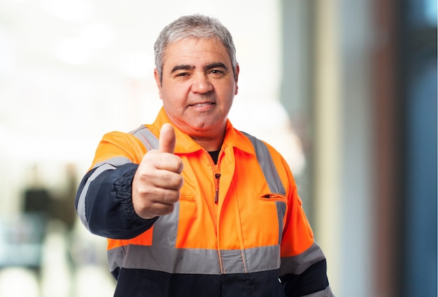 Old man with a reflective suit with thumb up Free Photo