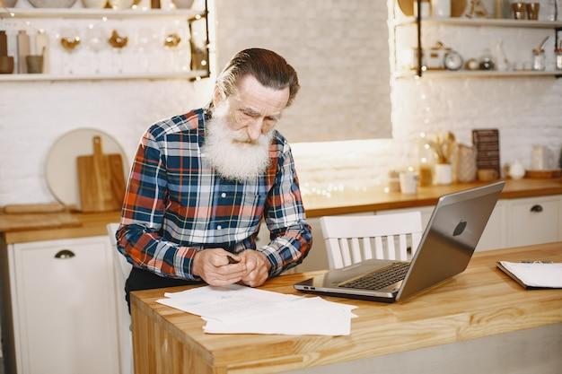 노트북과 노인입니다. 크리스마스 훈장에 앉아 할아버지입니다. 무료 사진