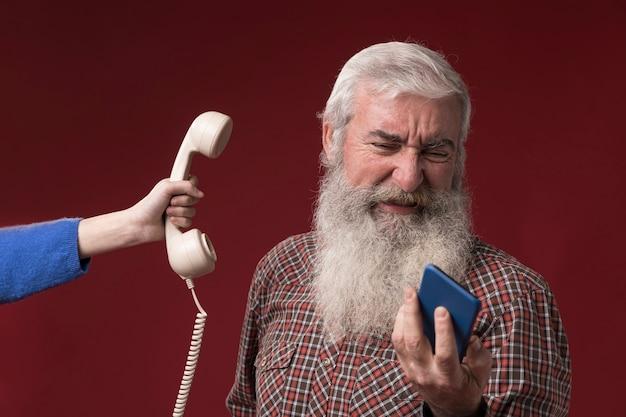 Vecchio con telefono nuovo e vecchio Foto Gratuite