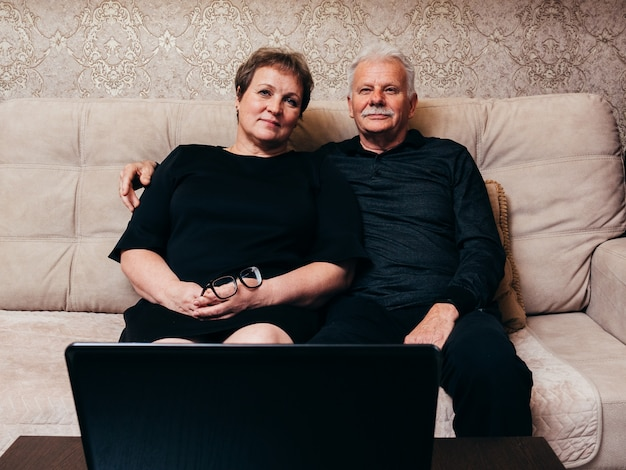 Old man and woman in black clothes are sitting at home in front of a  laptop. | Premium Photo