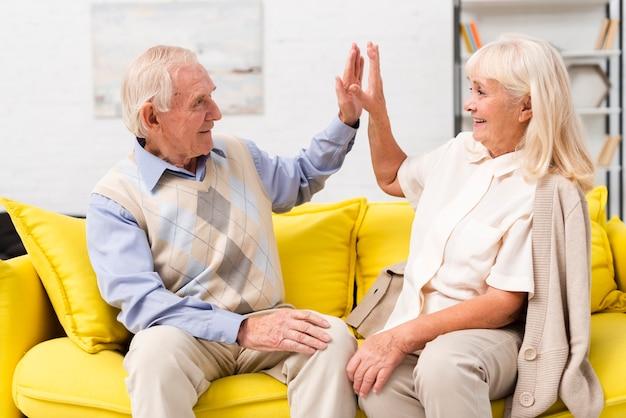 Alto fiving della donna e dell'uomo anziano sul sofà giallo Foto Gratuite