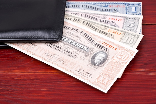 Old mexican pesos in the black wallet Premium Photo