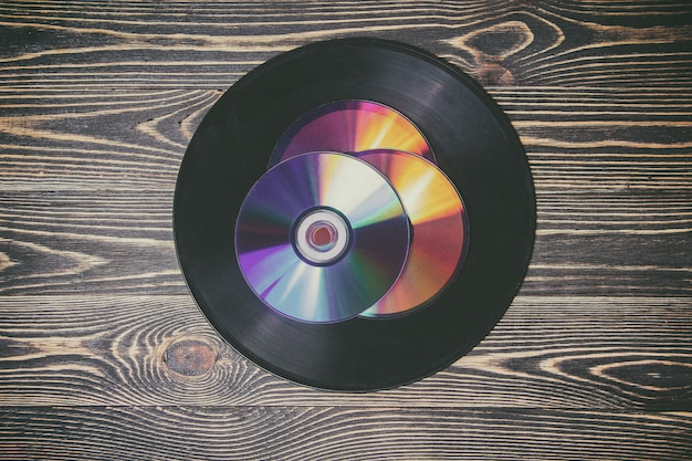 Old and morden audio disks on the wooden table Premium Photo