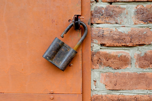 Old padlock on metal door. red brick wall Premium Photo