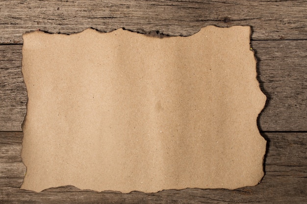 Old paper on brown aged wood Premium Photo