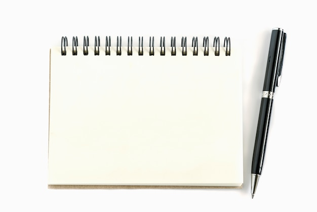 Paper notepad with black ballpoint pen on  white table