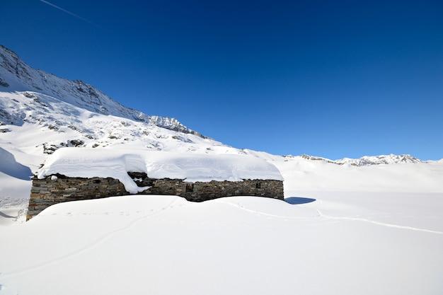 Old pasture huts in scenic winter background, winter in the alps Premium Photo