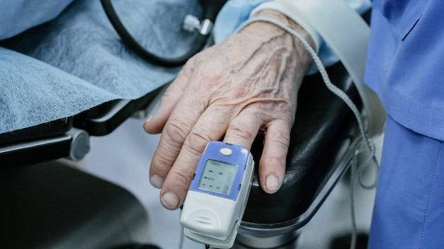 Old patient with pulse oximeter on finger for monitoring during surgery in hospital Premium Photo