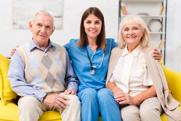 Old people sitting on yellow sofa with heir nurse Free Photo