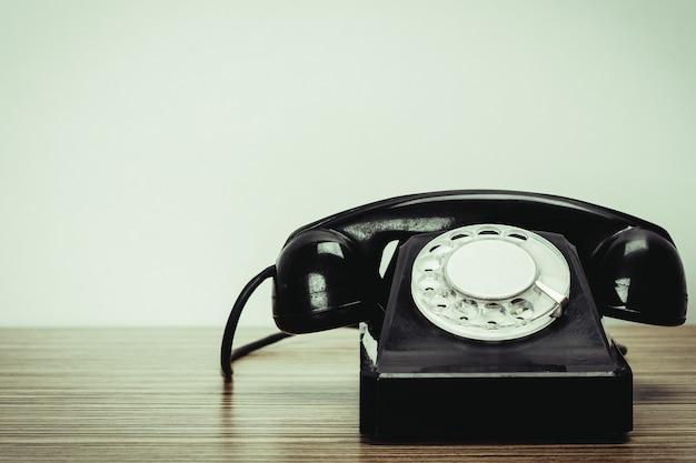 Старый телефон на деревянном столе Premium Фотографии