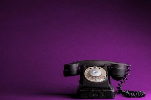 A old phone on the plastic pink backgrounds Premium Photo